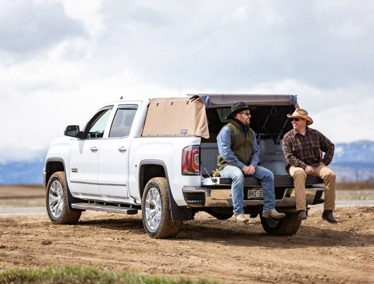Softopper equipped GMC with 2 ranchers sitting on the bed of the truck relaxing